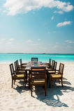 Table and chairs on exotic beach. Dinner Royalty Free Stock Photos