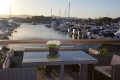 Table with chairs in front of a marina. Image of an elegant table and chairs in front of a marina full of luxurious yachts, taken in the evening stock images