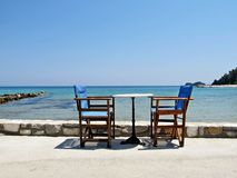 Table and chairs in front of the sea Royalty Free Stock Image