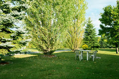 Table and chairs in the garden. Surrounded by green trees Royalty Free Stock Photos