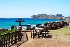 Table and chairs of a Greek taverna on the sea coast Stock Images