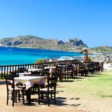 Table and chairs of a Greek taverna on the sea coast Stock Photography