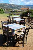 Table and chairs of a Greek taverna on the sea coast Royalty Free Stock Images