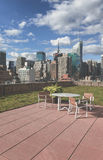 Table and Chairs on Green Rooftop with View of NYC Royalty Free Stock Image