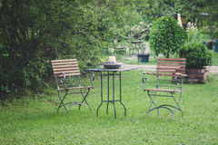 Table and chairs. On a lawn at the garden stock photo
