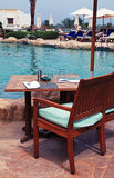Table and chairs near swimming pool. Table and chairs in empty cafe next to the resort swimming pool Royalty Free Stock Image