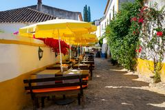 Table and chairs in open air street cafe or restaurant on narrow street of european town.  stock images