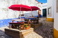 Table and chairs in open air street cafe or restaurant on narrow street of european town.  royalty free stock images