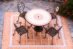 Table and chairs outdoors. Set of table and four chairs on an external terracotta patio viewed from above stock image