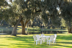 Table and chairs outside. White plastic table and chairs outside in a garden on green lawn by a pond or lake in the afternoon sun and a peaceful relaxing serene Royalty Free Stock Images