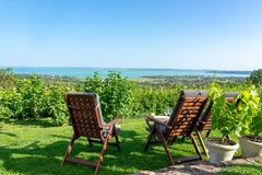 Table and chairs over the Lake Balaton on the hill romantic date, picnic, eating on nature. Csopak wine tasting. With view stock photography