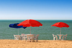 Table, chairs and parasol on the beach stock photo