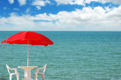 Table, chairs and parasol on  the beach Stock Image