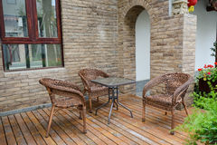 Table and chairs on planked ground before traditional building Royalty Free Stock Photo