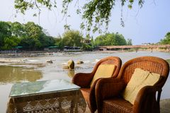 Table and chairs at riverside in sunny summer afternoon Royalty Free Stock Photos