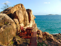Table and chairs are in the rock at sunset. Seychelles Stock Images