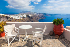 Table and chairs on roof with a panorama view on Santorini island, Greece. Royalty Free Stock Photography