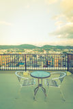 Table and chairs on  roof top terrace exterior .  ( Filtered ima Royalty Free Stock Photo
