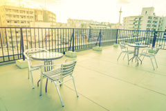 Table and chairs on  roof top terrace exterior .  ( Filtered ima Royalty Free Stock Image