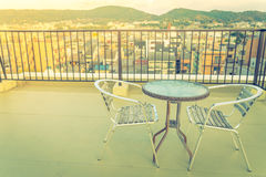 Table and chairs on  roof top terrace exterior .  ( Filtered ima Stock Photography