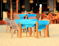 Table with chairs on sandy beach Royalty Free Stock Photography