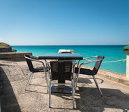 Table and chairs set for ocean view Royalty Free Stock Photography