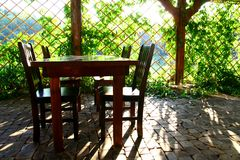 Table with chairs in the shadow Royalty Free Stock Photo