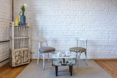 Table, chairs, shelves on the background of a white brick wall in vintage loft interior.  stock photo