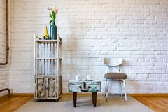 Table, chairs, shelves on the background of a white brick wall in vintage loft interior stock photo