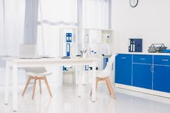 Table with chairs and shelves with documents at working place. In clinic stock photos