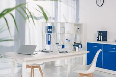 Table with chairs and shelves with documents at working place. In hospital stock photography