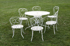 Table and chairs. Six iron chairs around a table on a garden lawn Stock Photo