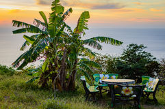 Table and chairs, stone outdoor furniture, picnic area on a hill with a beautiful view of the sea during sunset. Phuket, Thailand Stock Photo