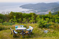 Table and chairs, stone outdoor furniture, picnic area on a hill with a beautiful view of the sea during sunset. Phuket, Thailand Royalty Free Stock Image