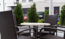 Table and chairs on street cafe terrace under rain Royalty Free Stock Photos