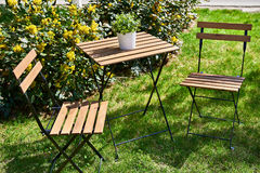 Table with chairs on summer lawn in garden Royalty Free Stock Photography