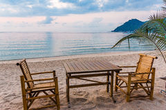 Table and chairs in the sunrise at a tanquil beach in Thailand. Thong Nai Pan Yai, Koh Pangan, Thailand, April , 2016, Table and chairs in the sunrise at a Stock Images
