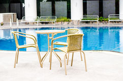 Table and chairs with swimming pool Stock Photo