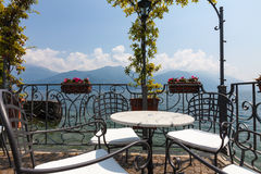 Table and chairs on a terrace overlooking lake and mountains in. Idyllic terrace with a table and four chairs overlooking lake Como in afternoon sunlight under a Royalty Free Stock Photography