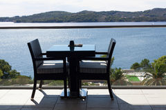 Table and chairs on terrace with sea view Royalty Free Stock Photography