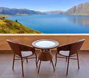 Table and chairs on a terrace, view on a lake Royalty Free Stock Images