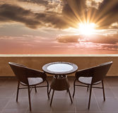 Table and chairs on a terrace, view on sunset Stock Images