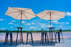 Table and chairs and umbrellas take photography looking up. Outdoors on blue sky background royalty free stock photography