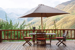 Table and chairs under umbrella on terrace against awesome mount royalty free stock photo