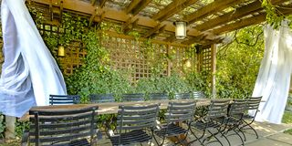 Table and chairs under a wooden pergola stock photos