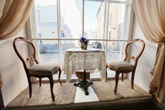 Table and chairs by window in empty cafe Royalty Free Stock Photo