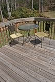 Table And Chairs On Wood Deck. A table and chairs on wood board deck with wood railing Royalty Free Stock Photography