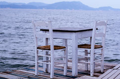 Table and chairs on wooden jetty stock photo