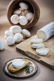 Table with cheese. Cheese table with knife, rosemary and mushroons Royalty Free Stock Images