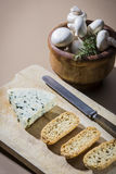 Table with cheese. Cheese table with knife, rosemary and mushroons Royalty Free Stock Photos